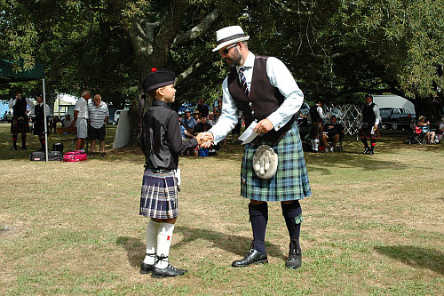 Dr Brendon Eade presenting 1st prize in the Novice Grade March to his son Seumas at the Paeroa Solo Piping competition, February 2016.